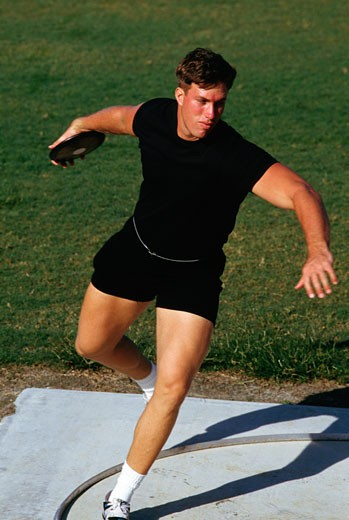 Young man preparing to throw a discus : Stock Photo