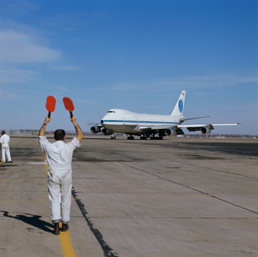 Signalman Bringing in 747 Airplane : Stock Photo