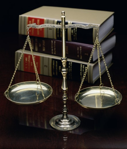 Stock Photo: 287-126C Close-up of a weighing scale in front of a stack of law books