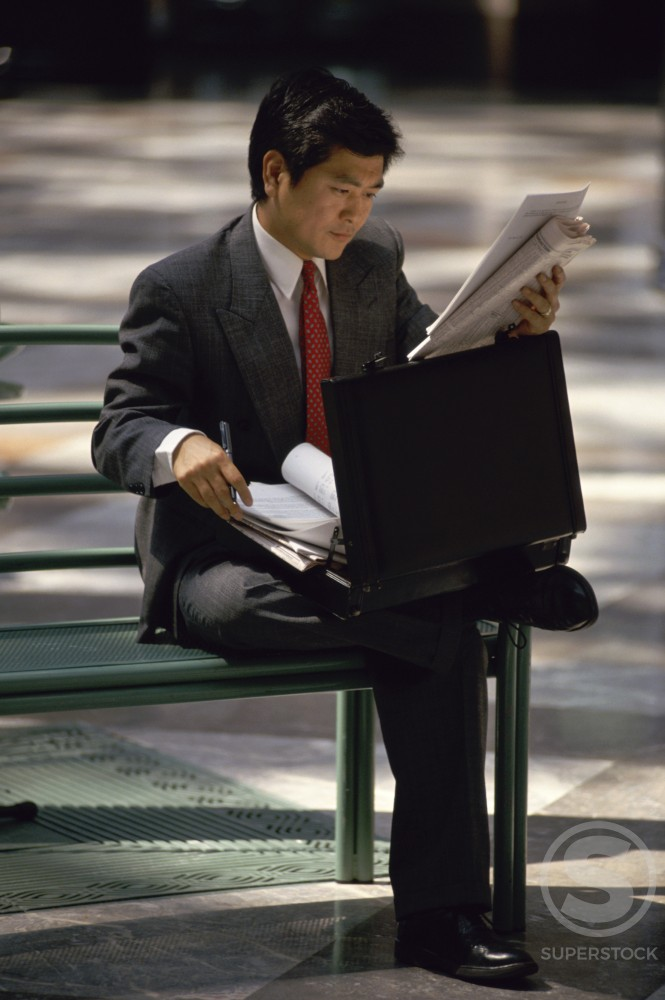 Businessman sitting on a bench and reading a newspaper : Stock Photo
