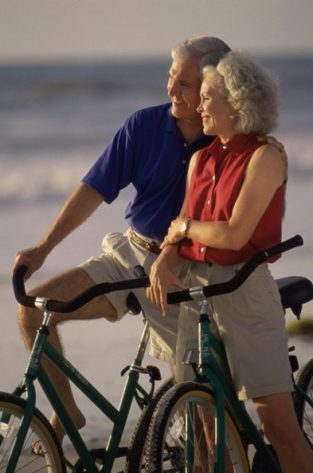 Senior couple with bicycles on the beach : Stock Photo