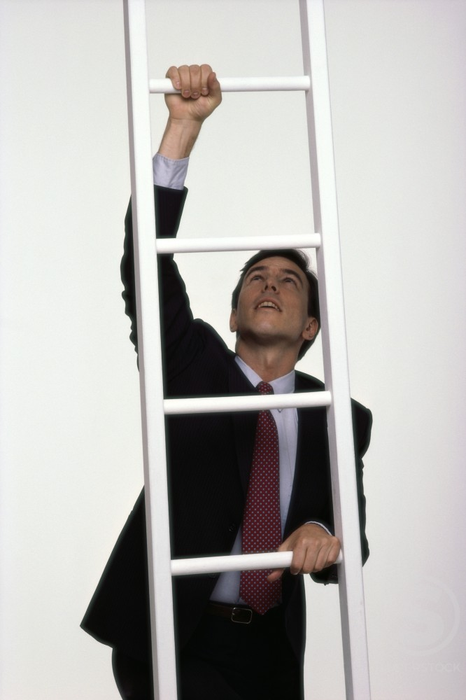 Businessman climbing up a ladder : Stock Photo