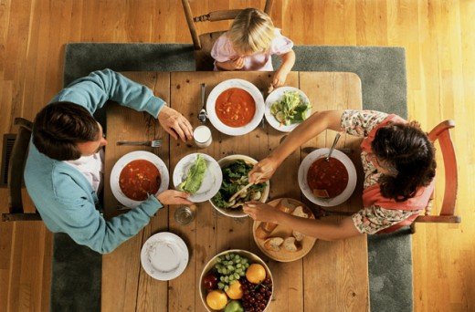 High angle view of a girl eating food with her parents at a dining table : Stock Photo