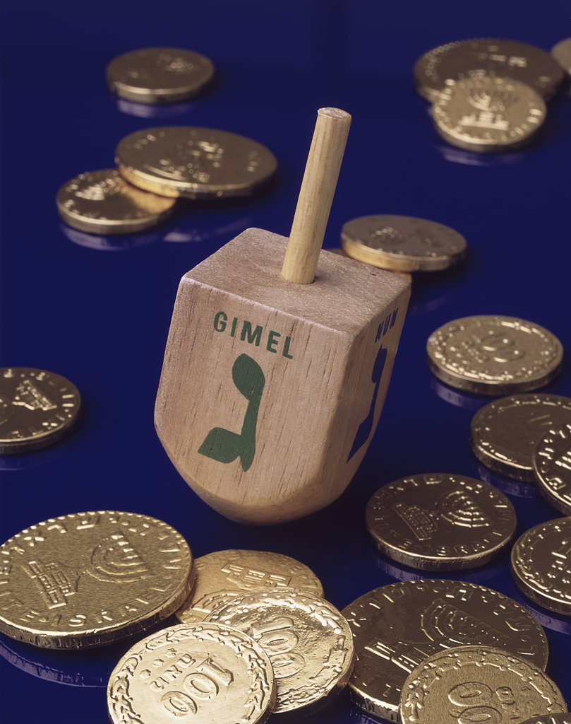 Stock Photo: 291-1869A Close-up of a Hanukkah dreidel with Hanukkah gelts