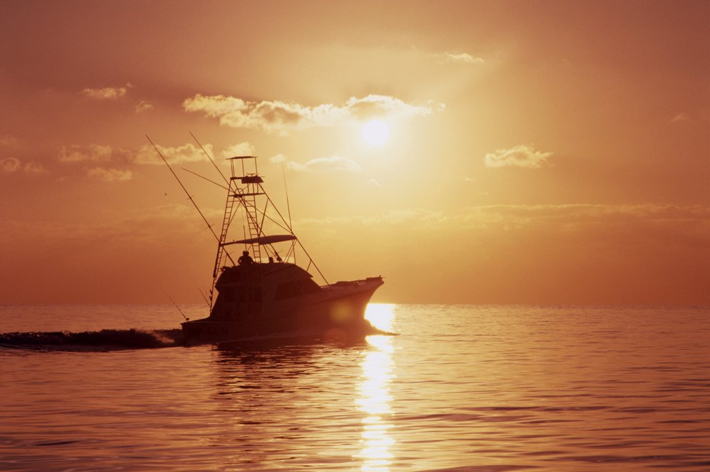 Silhouette of a fishing boat in the sea at sunset : Stock Photo