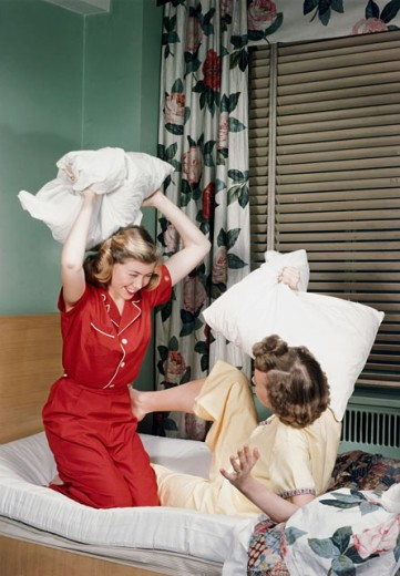 Two teenage girls having a pillow fight in a bedroom : Stock Photo