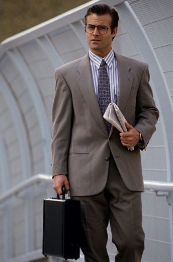 Portrait of a businessman holding a briefcase and newspaper : Stock Photo