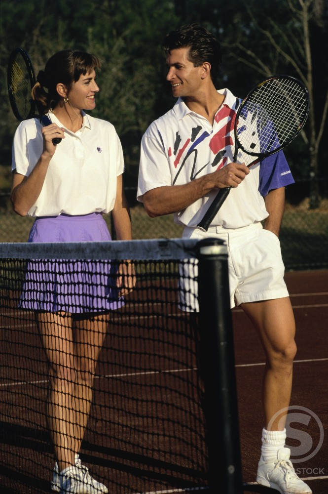 Young couple holding tennis rackets and talking to each other : Stock Photo