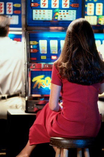 Rear view of a woman playing a slot machine in a casino : Stock Photo