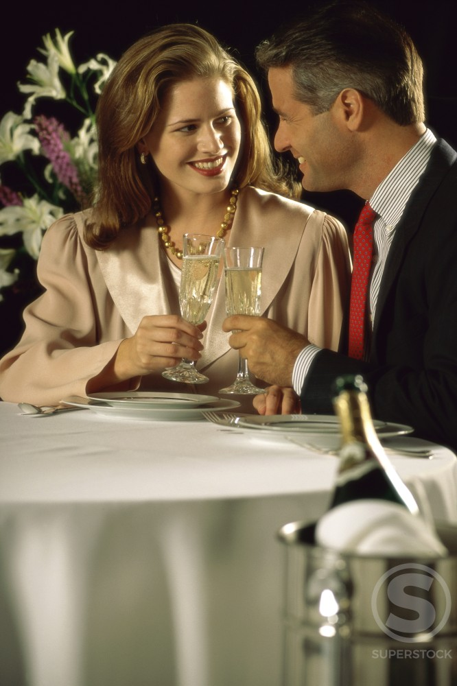 Stock Photo: 294-842A Mid adult couple toasting with champagne in a restaurant