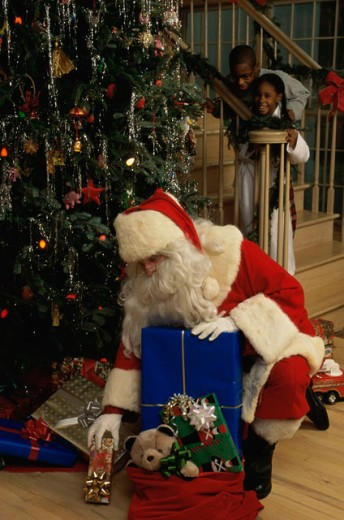 Stock Photo: 295-395C Santa Claus putting Christmas presents under a Christmas tree