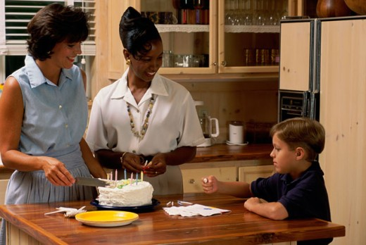 Stock Photo: 295-645C Mother cutting a cake with her son and a mid adult woman in a kitchen