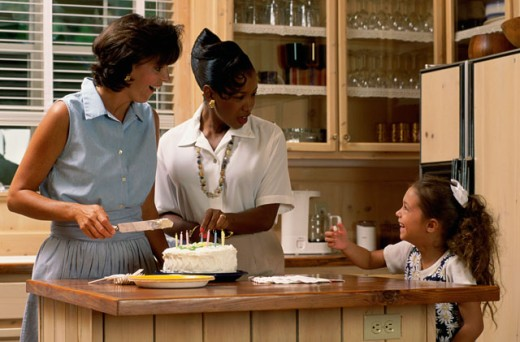 Mother cutting a cake with her daughter and a mid adult woman in a kitchen : Stock Photo