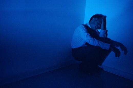 Stock Photo: 295-871 Businessman crouching in the corner of a room and crying