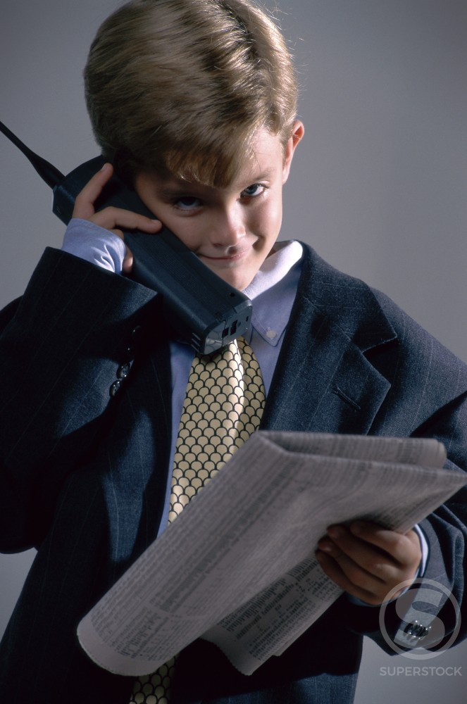 Stock Photo: 295-992 Boy dressed as a businessman using a cordless phone