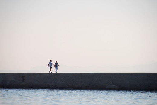Stock Photo: 3138-536954 Two people walking on a jetty at dawn, Mytilene, Lesbos, Greece