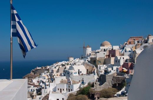 Greek flag with a town at the waterfront, Santorini, Cyclades Islands, Greece : Stock Photo