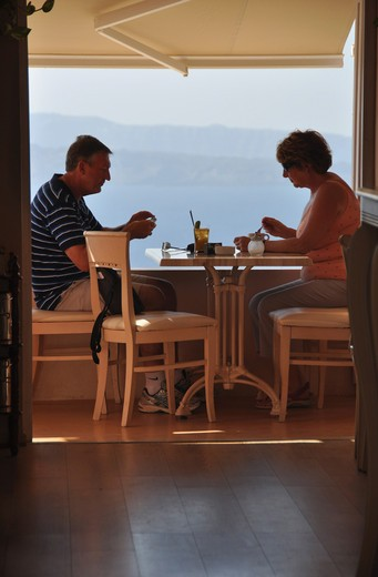 Couple eating food in restaurant, Oia, Santorini, Cyclades Islands, Greece : Stock Photo