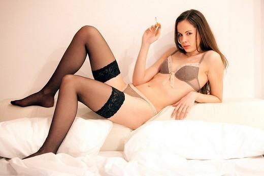 ragazza in intimo che fuma a letto : Stock Photo
