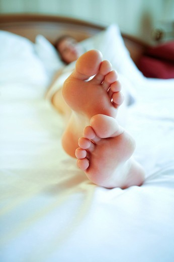 feet of a young woman in the bed : Stock Photo