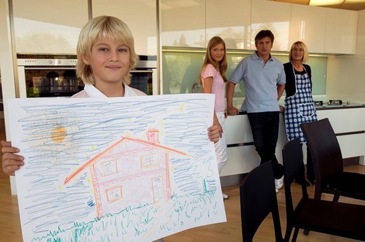 Stock Photo: 3153-590642 family in the kitchen, boy showing a drawing