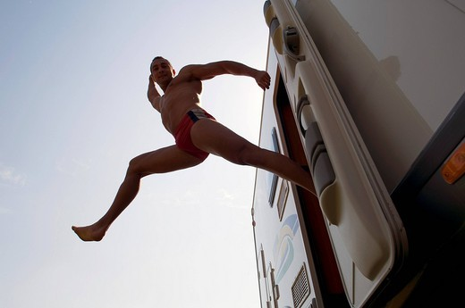 young man jumping from a camper : Stock Photo