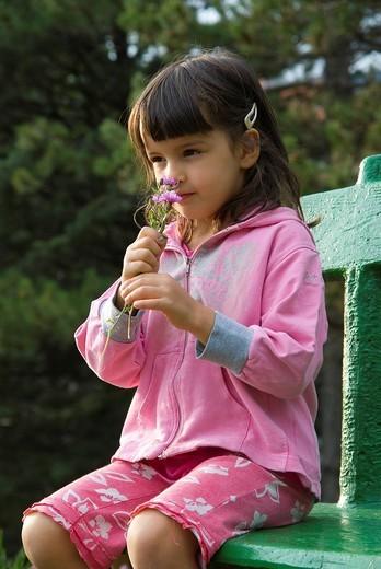 little girl smelling flowers : Stock Photo