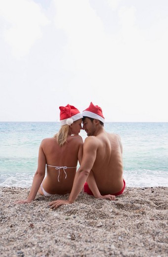 couple by the sea with christmas hats : Stock Photo