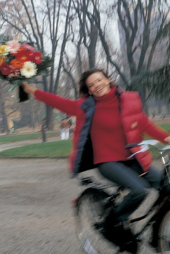 woman riding bicycle with a bunch of flowers : Stock Photo