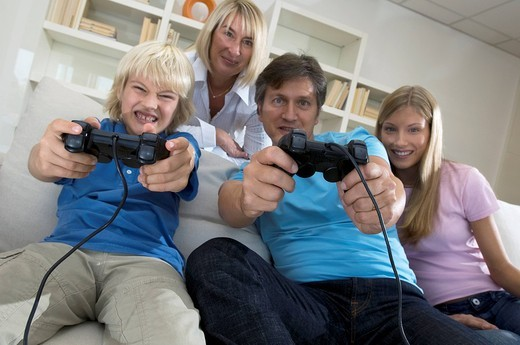 family in livingroom, father and son playing with playstation : Stock Photo