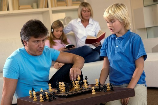 Stock Photo: 3153-653096 family in livingroom, father and son playing chess