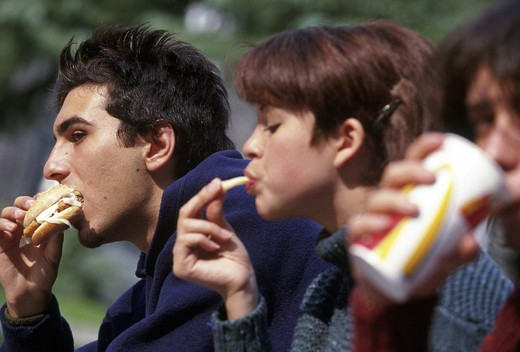 teenagers eating outdoors : Stock Photo