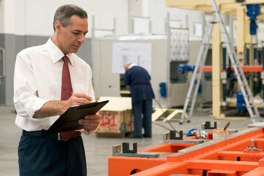 Stock Photo: 3153-667841 man with clipboard standing in warehouse