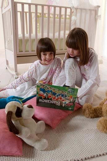 little girls reading a book, pyjama : Stock Photo