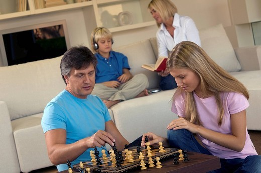 family in livingroom, father and daughter playing chess : Stock Photo