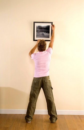 man hanging a picture : Stock Photo
