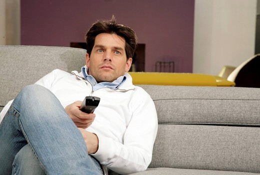 man sitted on divan with remote control : Stock Photo