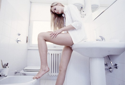 Stock Photo: 3153-704028 Young woman applying lotion to leg â