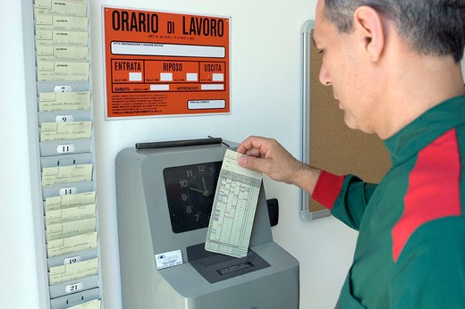 Stock Photo: 3153-706908 worker place timecards in clocking in machine