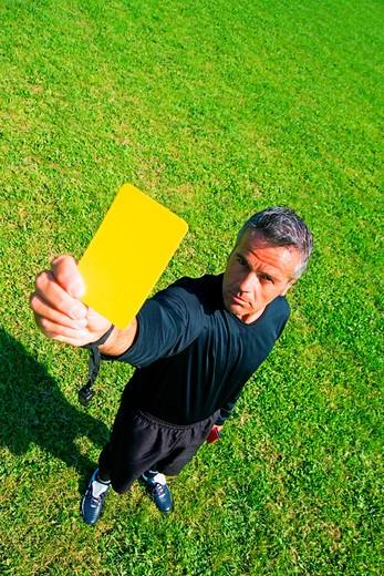 football referee holding up yellow card : Stock Photo