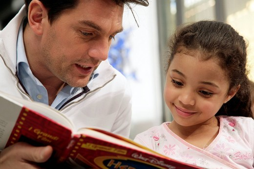 man and little girl reading a book : Stock Photo