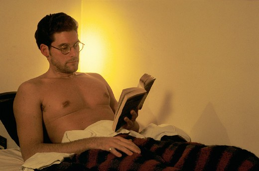 man reading in the bed : Stock Photo