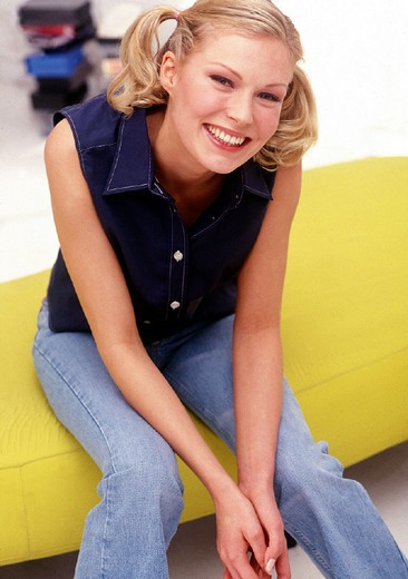 young womang sitting on a yellow sofa : Stock Photo