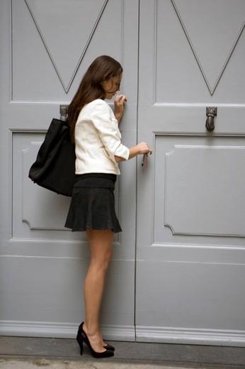donna cha apre un portone : Stock Photo