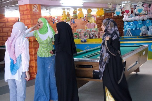 Stock Photo: 3153-777671 dubai UAE mall al safa park girl in traditional dress enjoy playing billiard