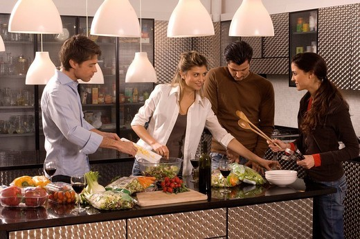 Stock Photo: 3153-783821 young women and men in kitchen, preparing the dinner together