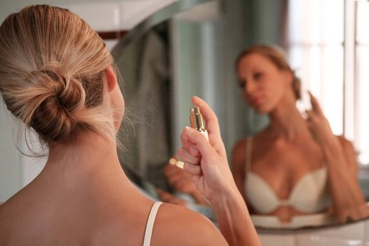 Stock Photo: 3153-787567 young woman spraying perfume on neck