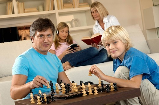 family in livingroom, father and son playing chess : Stock Photo