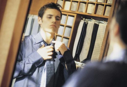 Stock Photo: 3153-814974 young man choosing ties in a shop