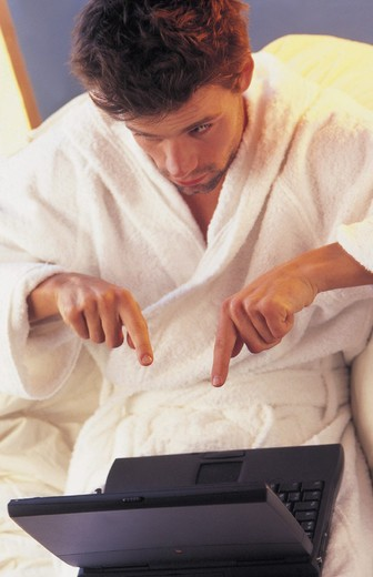 Stock Photo: 3153-816276 man wearing bathrobe,  portable computers